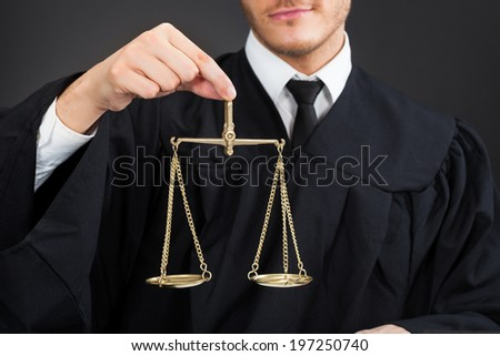 Midsection of male judge holding weight scale against black background - stock photo