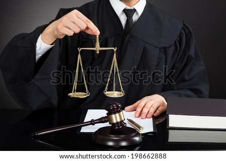 Midsection of male judge holding weight scale at desk against black background - stock photo