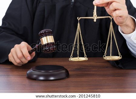 Midsection of male judge holding weight scale while striking gavel on block at desk in courtroom - stock photo