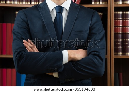 Midsection of male lawyer standing against bookshelf in courtroom - stock photo