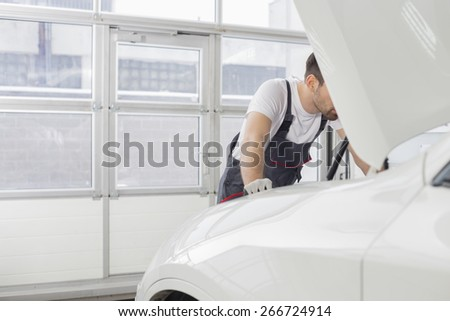 Midsection of male technician repairing car engine in workshop - stock photo