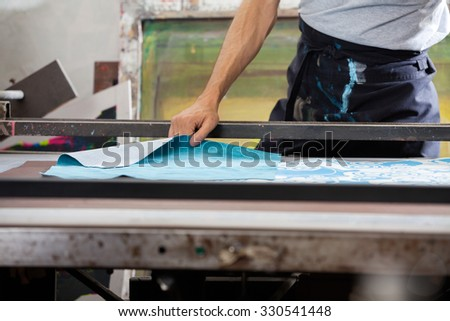 Midsection of male worker designing paper in factory - stock photo