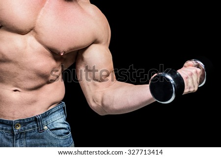 Midsection of man exercising lifting dumbbells against black background - stock photo