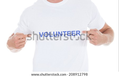 Midsection of man pointing at his volunteer tshirt over white background - stock photo