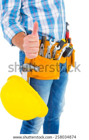 Midsection of manual worker gesturing thumbs up on white background - stock photo