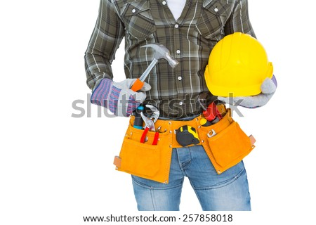 Midsection of manual worker wearing tool belt while holding hammer and helmet on white background - stock photo