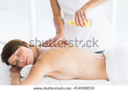 Midsection of masseur pouring oil on naked woman back at spa