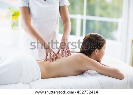 Midsection of masseuse giving back massage to naked woman at spa