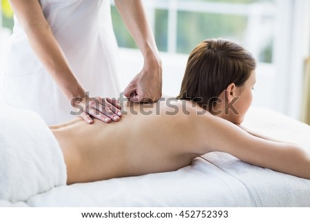 Midsection of masseuse giving back massage to woman at spa