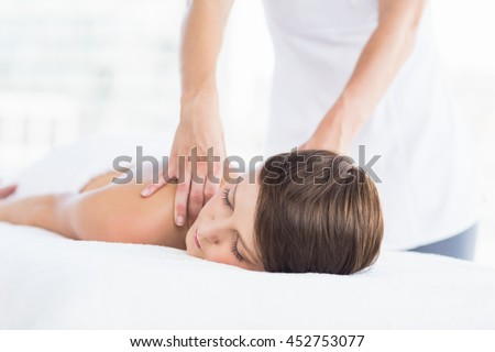 Midsection of masseuse giving massage to naked woman at spa
