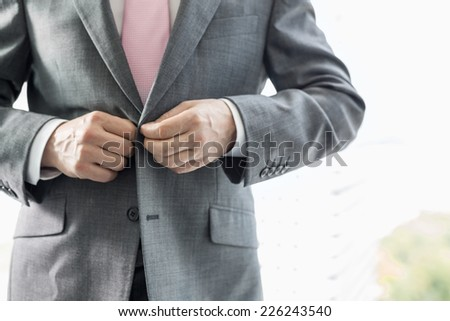 Midsection of mature businessman buttoning his blazer - stock photo
