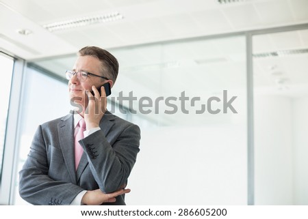 Midsection of mature businessman buttoning sleeve - stock photo