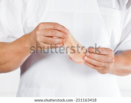 Midsection of mature butcher holding chicken meat in shop