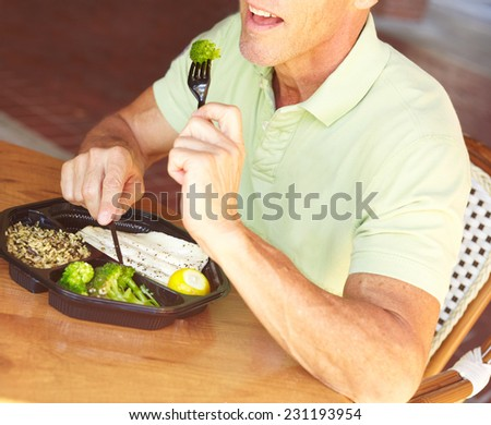 Midsection of mature man eating broccoli served with tilapia at restaurant