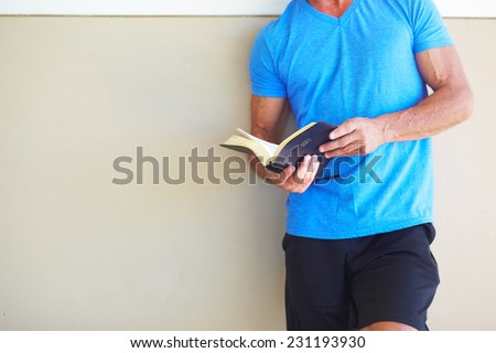 Midsection of mature man reading Bible while leaning on wall - stock photo