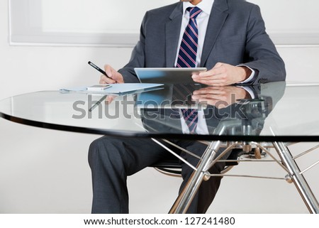 Midsection of mid adult businessman using digital tablet at desk in office - stock photo