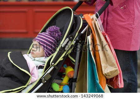 Midsection of mother with cute baby in stroller - stock photo