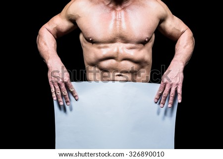 Midsection of muscular man holding white blank paper against black background - stock photo