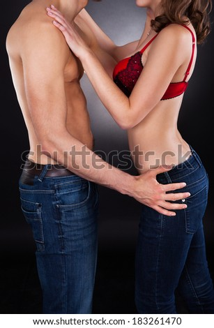 Midsection of passionate young couple standing isolated over black background - stock photo