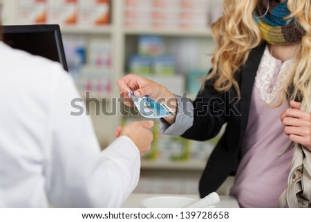 Midsection of pharmacist receiving money from woman for medicines - stock photo