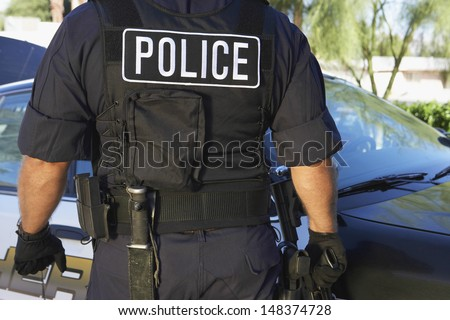 Midsection of policeman in uniform standing against car - stock photo