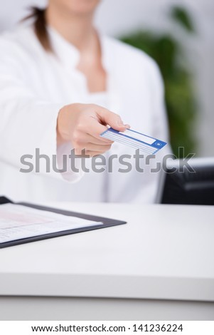 Midsection of receptionist giving credit card at counter in hospital - stock photo