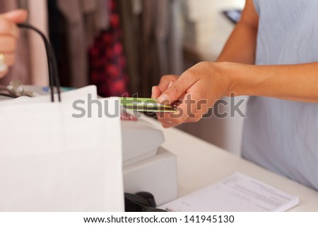 Midsection of saleswoman holding credit card from customer while using cash desk at boutique counter - stock photo