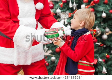 Midsection of Santa Claus giving gift to boy against Christmas tree - stock photo