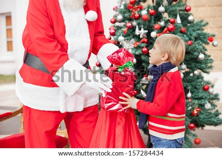 Midsection of Santa Claus giving present to boy against Christmas tree - stock photo