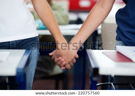 Midsection of schoolboy and girl holding hands at desk in classroom