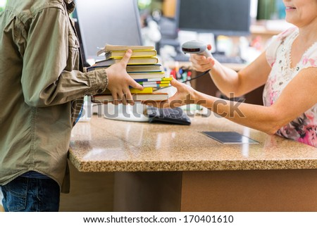 Midsection of schoolboy holding books while librarian scanning them at checkout counter in library - stock photo