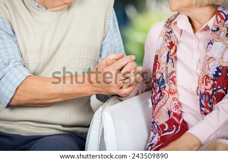 Midsection of senior couple holding hands while sitting on chairs at nursing home porch - stock photo