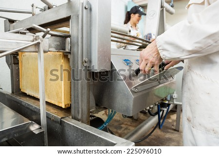 Midsection of senior female beekeeper operating honey extraction plant in factory - stock photo
