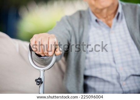 Midsection of senior man holding metal walking stick at nursing home - stock photo