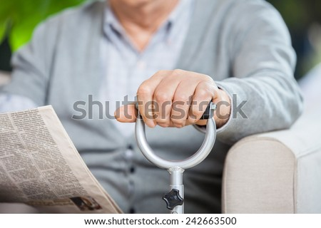 Midsection of senior man with newspaper and metal cane sitting on couch at nursing home porch - stock photo