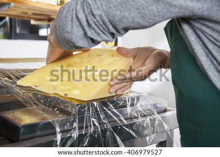 Midsection Of Senior Salesman Packing Cheese
