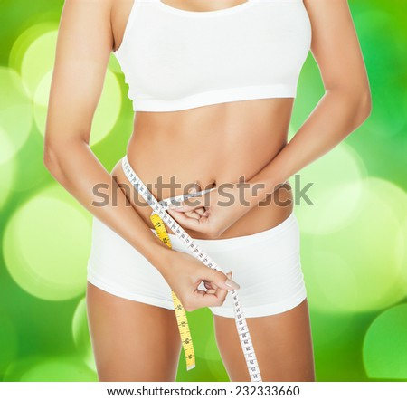 Midsection of slim woman in innerwear measuring waist with measure tape against green background - stock photo