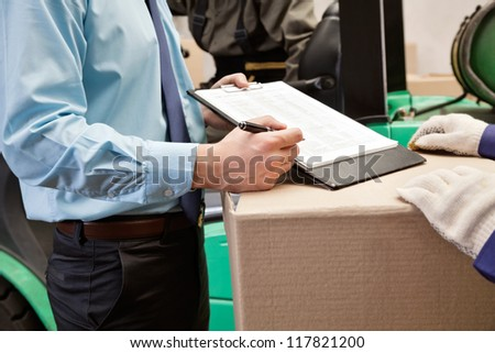 Midsection of supervisor showing clipboard to young foreman at warehouse - stock photo