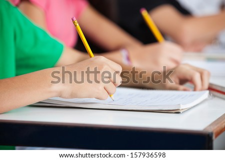 Midsection of teenage classmates writing in book at desk - stock photo