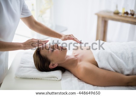 Midsection of therapist performing reiki on young woman at spa - stock photo
