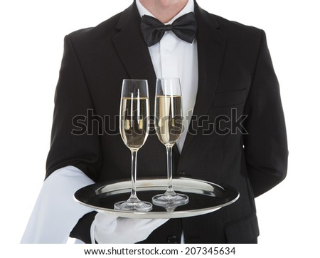 Midsection of waiter carrying champagne flutes on tray over white background - stock photo