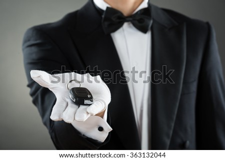 Midsection of waiter holding car key while standing against gray background - stock photo