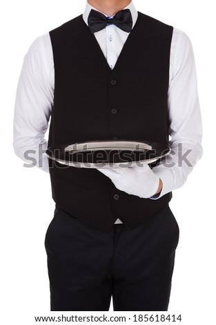 Midsection of waiter holding empty tray over white background - stock photo