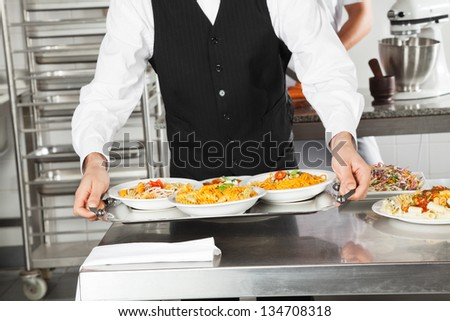 Midsection of waiter holding pasta dishes in tray at restaurant kitchen