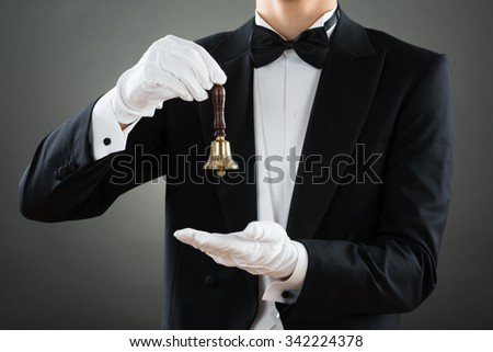 Midsection of waiter holding ring bell while standing against gray background - stock photo