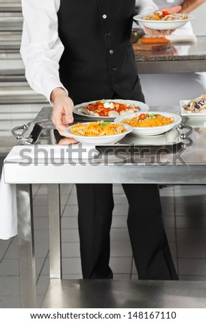 Midsection of waiter placing pasta dishes on tray in commercial kitchen