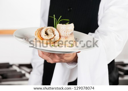 Midsection of waiter presenting salmon roll in kitchen