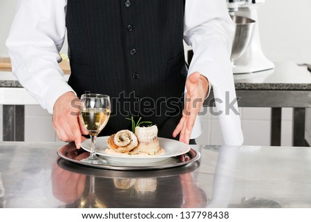 Midsection of waiter with salmon roll and white wine standing by kitchen counter