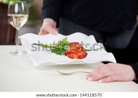 Midsection of waitress serving salmon dish at restaurant table - stock photo
