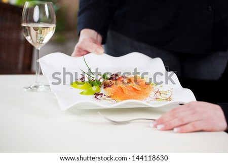 Midsection of waitress serving salmon dish to customer at table - stock photo